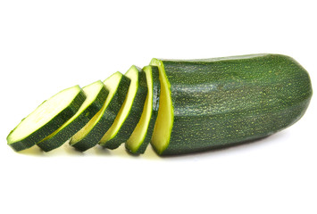 Half zucchini with some slices on white background.