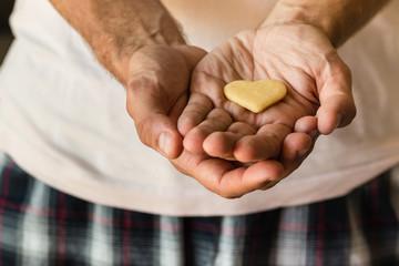 man holding biscuit heart in hands