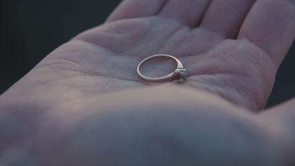 Wedding rings on the palm of the groom, marriage proposal from