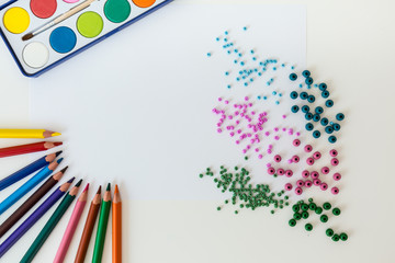 Crayons and paints on a table
