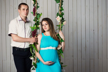 Portrait of a pregnant woman with the husband on a swing in the