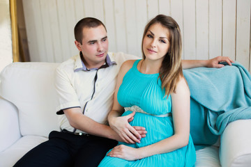 Home portrait of a pregnant woman with her husband