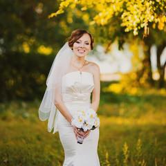 Adorable young caucasian bride in garden, sunny summer day.