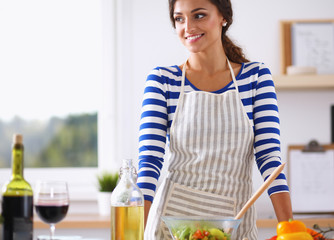 Smiling young woman  mixing fresh salad, standing near desk
