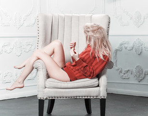 sexy woman in a red sweater lying in a chair