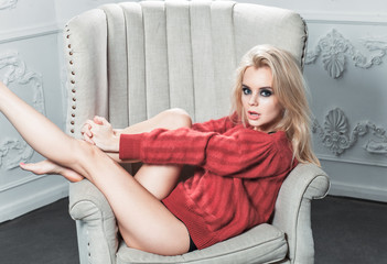 sexy girl in a red sweater lying in a chair