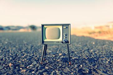 何もない道路の上に置かれた古いテレビ