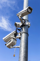 four cctv installed on metal light pole, vertical photo on blue