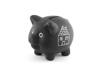Black piggy bank with drawing of house. Clipping path included.