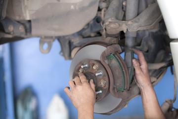 bear hands fixing car wheel hub, disc brake