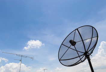 circular signal receiver disc and television antenna on blue sky