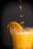 Fotoroleta Orange flavoured soft drink splashing over the glass.