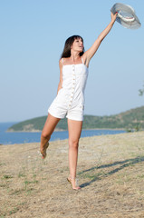 Woman dressed in white, with hat, standing relaxed at sunny day