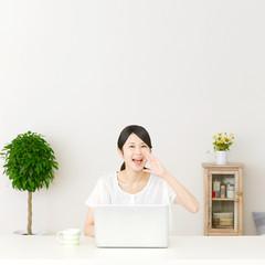 パソコンの前に座って呼びかける女性