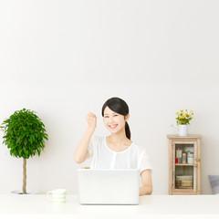パソコンの前に座ってガッツポーズする女性