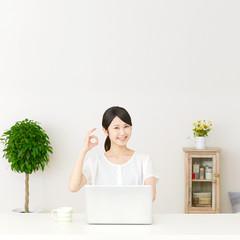 パソコンの前に座ってOKサインする女性