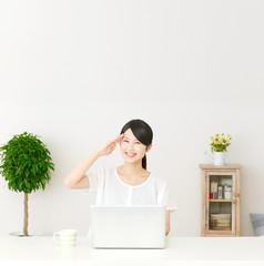パソコンの前に座って敬礼する女性