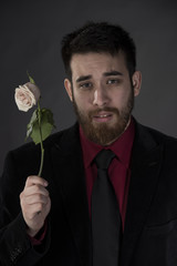 Sad Man in Formal Wear Holding Withered Rose