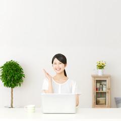 パソコンの前に座って案内する女性
