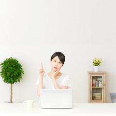 パソコンの前に座って指差す考える女性