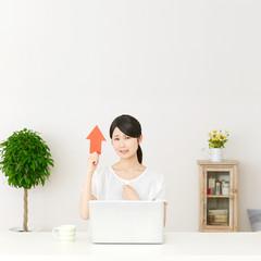 パソコンの前に座って矢印で指す困った女性