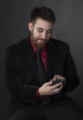 Smiling Man in Formal Attire with Phone