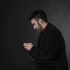 Man in Formal Attire with Phone in Side View