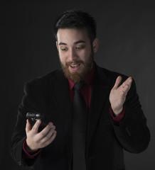 Surprised Businessman Looking at his Phone