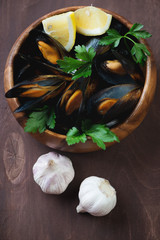 Wooden bowl with boiled mussels, close-up, studio shot