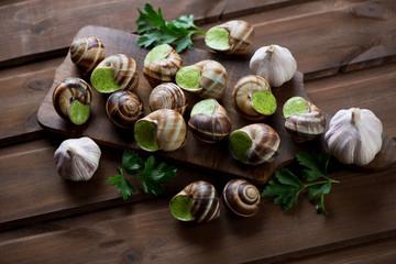 Bourguignonne snail au gratin over rustic wooden surface