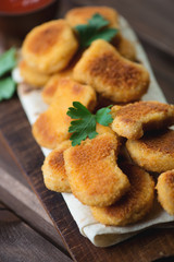Close-up of chicken nuggets with fresh parsley, vertical shot