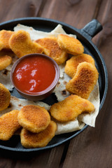 Chicken nuggets with dip sauce in a frying pan, close-up