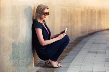 Young fashion woman with tablet computer sitting at the wall