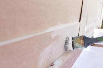 paintbrush painting white on wood fence