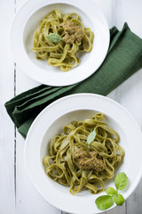 Tagliatelle with pesto sauce over white wooden surface