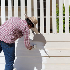 worker painted white fence with brush