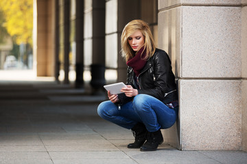 Young fashion woman using tablet computer at the wall