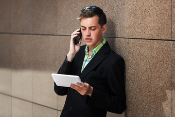 Young man with tablet computer calling on mobile phone