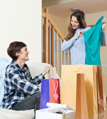 Happy  woman and man with clothing and shopping bags
