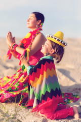 Toned photo of son and mother dressed in Mexican clothes praying