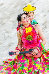 son hugging his mother in Mexican costume and playing the guitar