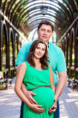 Portrait of beautiful loving couple awaiting baby. Husband and