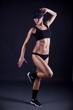 sports woman portrait wearing black sportswear on black backgrou