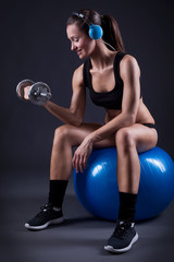 Fitness young woman sitting on the ball lift weights and listeni