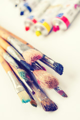 paintbrushes closeup and oil multicolor paint tubes on white art