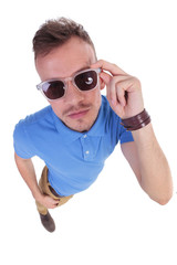 casual young man holds his sunglasses