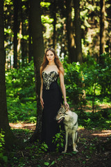 portrait of a girl in a dark dress with a dog in the forest