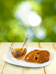 image of a cup of tea and buns on a table on a green background
