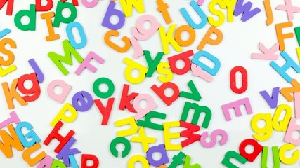 Alphabet magnets being shuffled around, stop motion