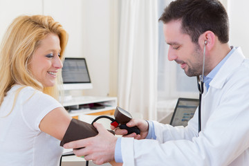 Young attractive doctor checking patient's blood pressure